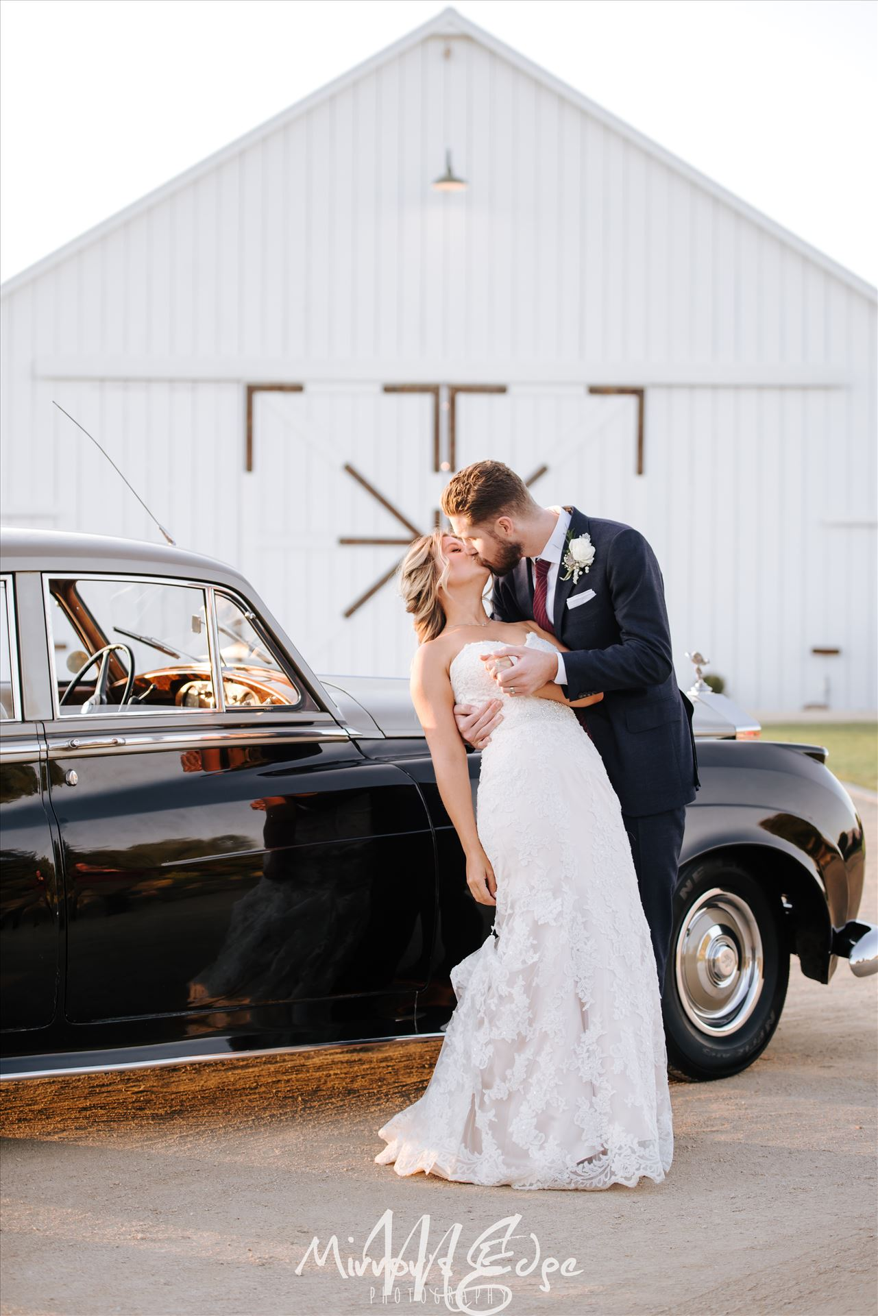 Port-7511.JPGWhite Barn in Edna Valley rustic chic wedding by Mirror's Edge Photography, San Luis Obispo County Wedding and Engagement Photographer.  Dip and kiss with Bride and Groom and Rolls Royce Wedding in front of the White Barn.