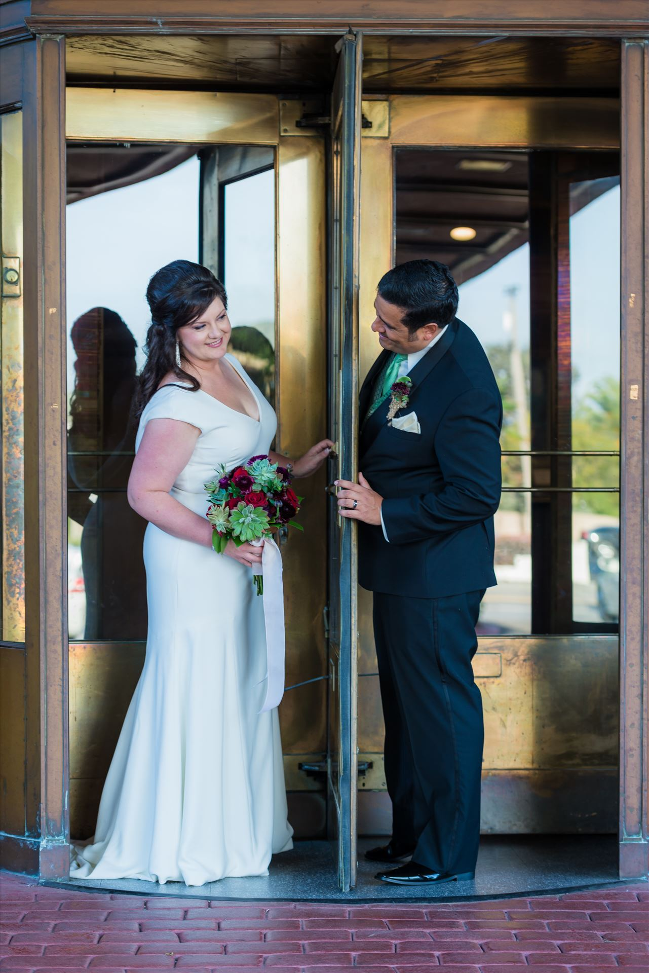Mary and Alejandro 13 - Wedding photography at the Historic Santa Maria Inn in Santa Maria, California by Mirror's Edge Photography. Bride and Groom revolving door entrance. by Sarah Williams