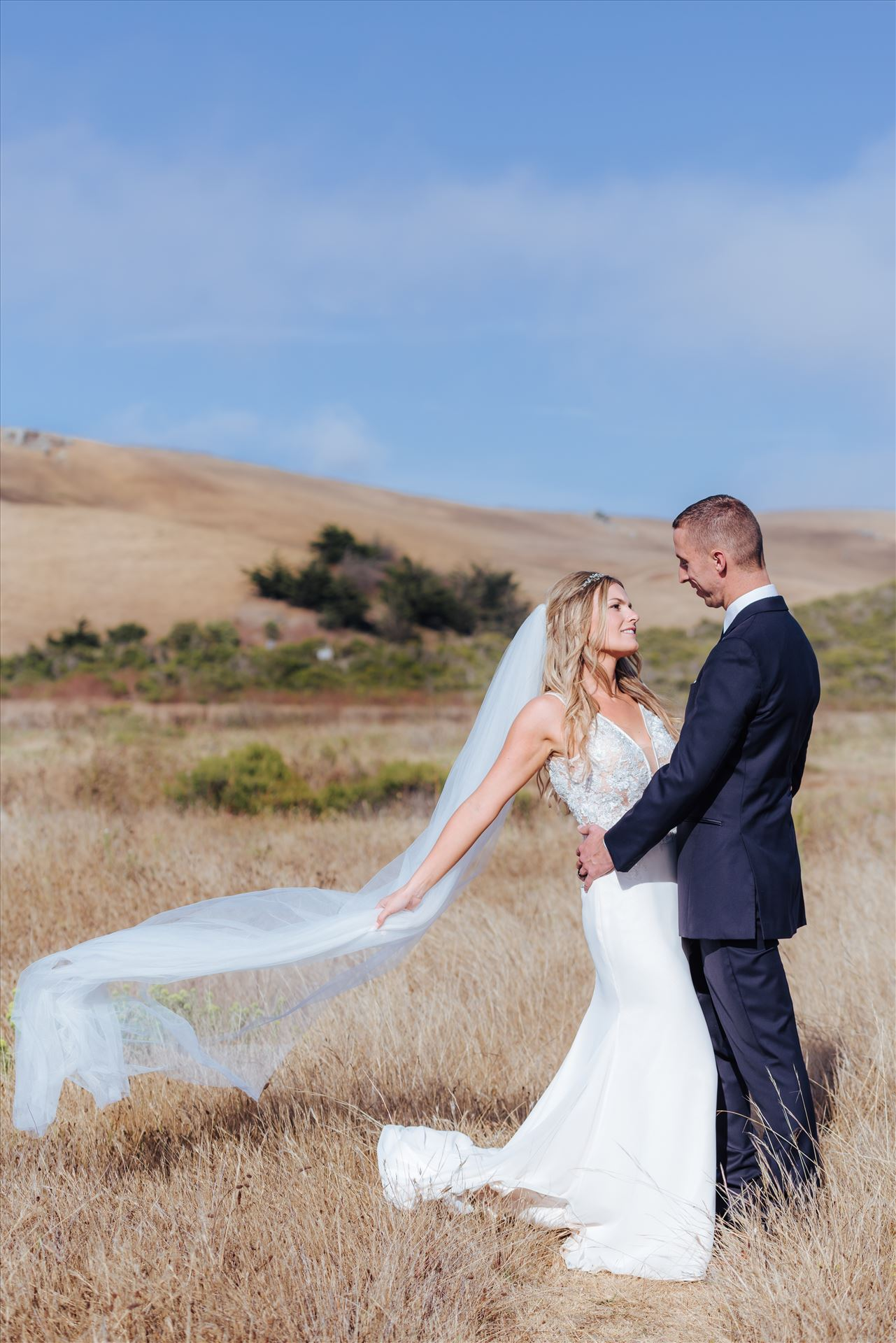 FW-0776.JPGCayucos California Beach and Bluffs Wedding near Morro Bay and Cambria with romantic chic flair by Mirror's Edge Photography, San Luis Obispo County Wedding Photographer.  Bride and Groom on the bluffs overlooking the ocean with veil flowing in the wind.