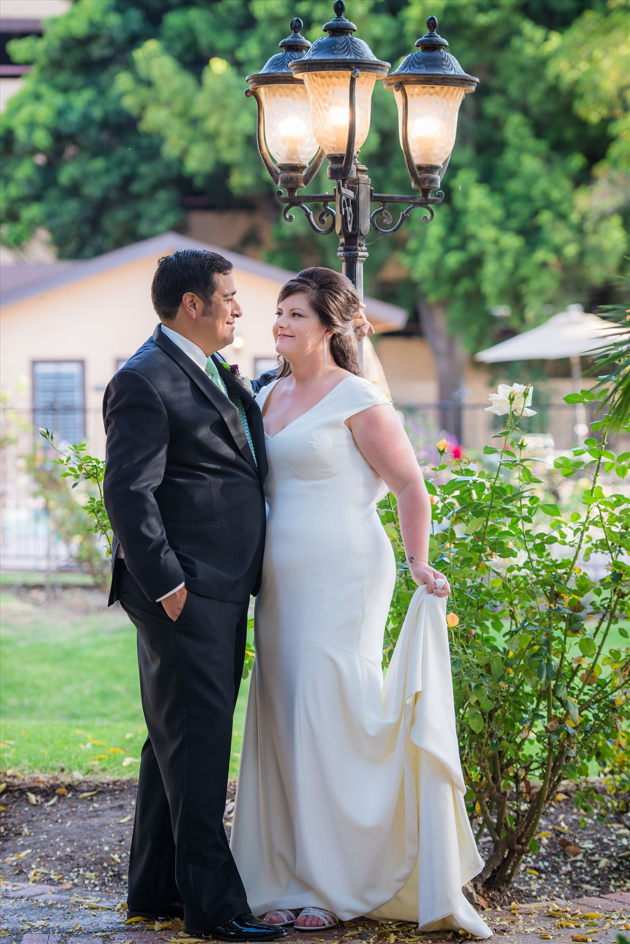 Mary and Alejandro 21 - Wedding photography at the Historic Santa Maria Inn in Santa Maria, California by Mirror's Edge Photography. Bride and Groom at the lamppost near back lawn. by Sarah Williams