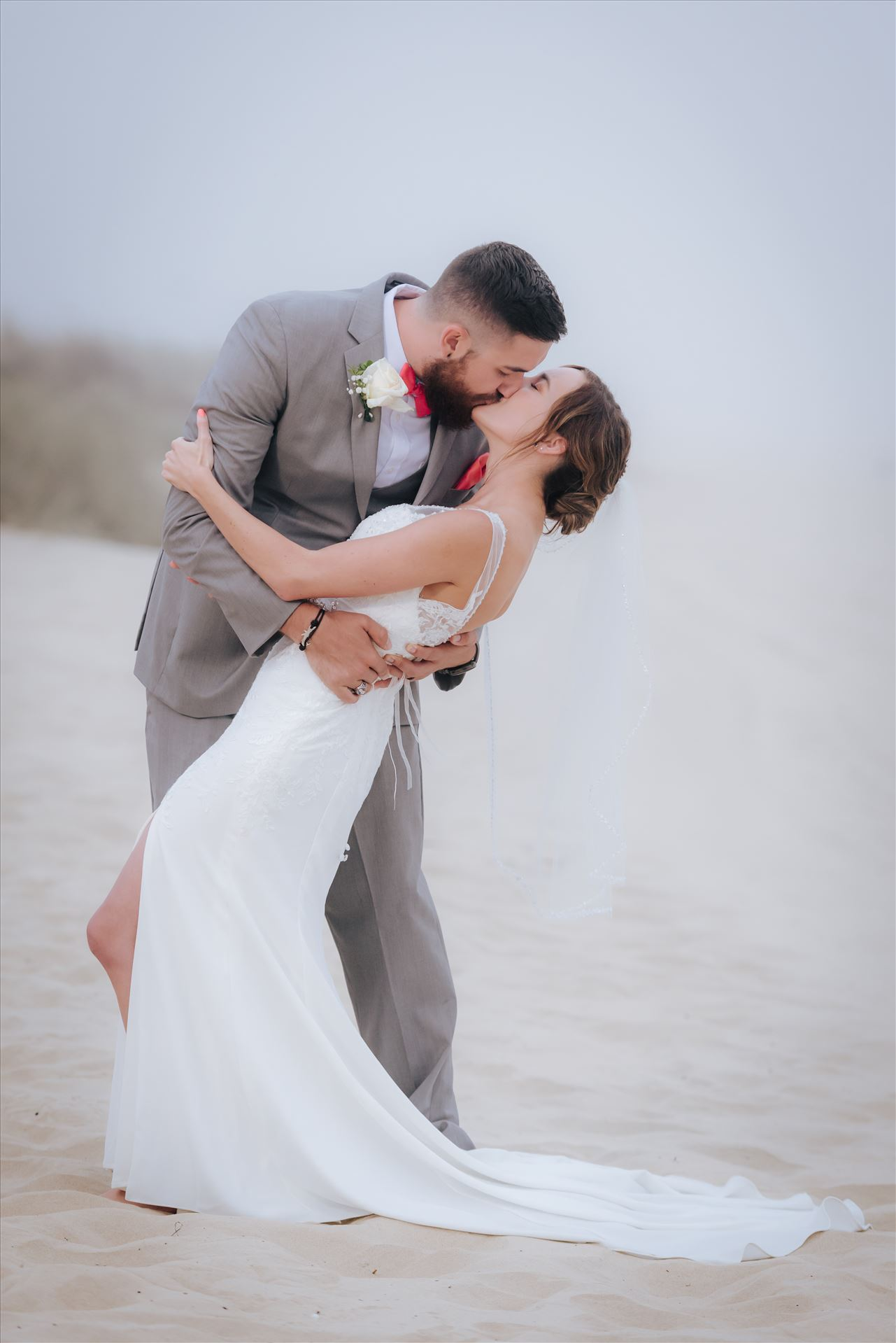 FW-8130.jpg - Romantic wedding in the sand on Grover Beach in California.  Barefoot with surfboards and driftwood, tent and ceremony set up by Beach Butlerz, wedding photography by Mirror's Edge Photography.  Romantic Bride and Groom dip in the fog by Sarah Williams