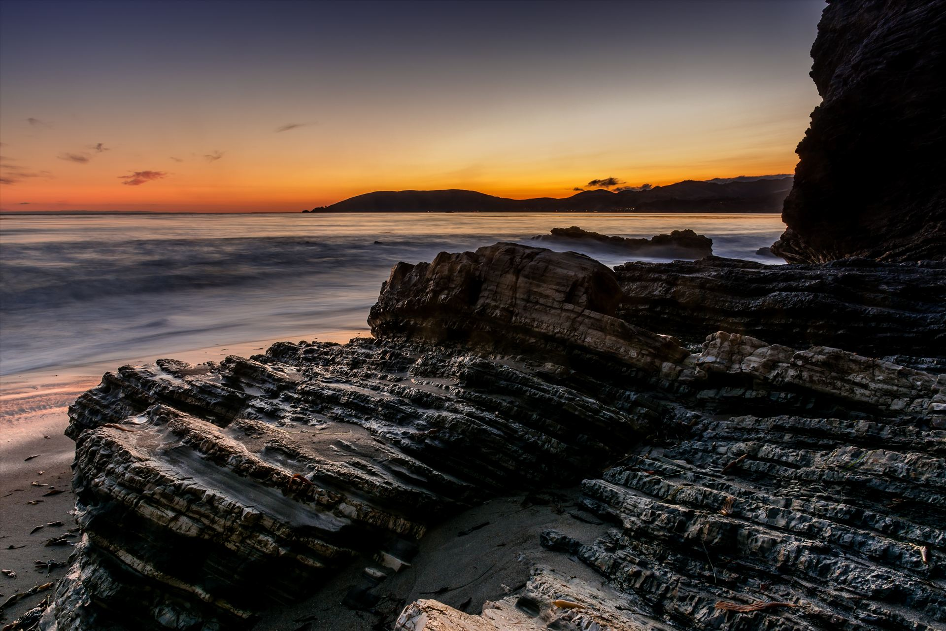 Avila in the Distance.jpg - Spyglass cliffs at sunset with Avila Beach in the distance by Sarah Williams