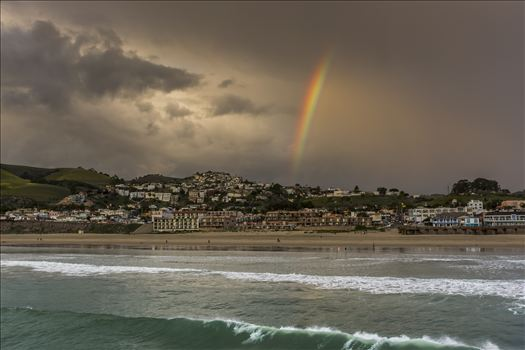 Rainbow's end over downtown Pismo Beach - where ocean and sand meet stormy sky.