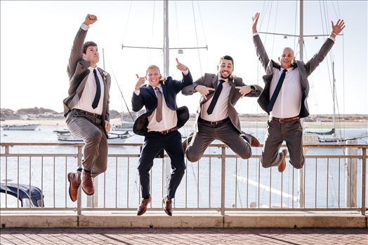Sarah Williams of Mirror's Edge Photography, a San Luis Obispo Wedding and Engagement Photographer, captures Ryan and Joanna's wedding at the iconic Windows on the Water Restaurant in Morro Bay, California.  Groomsmen jump in front of Morro Rock.