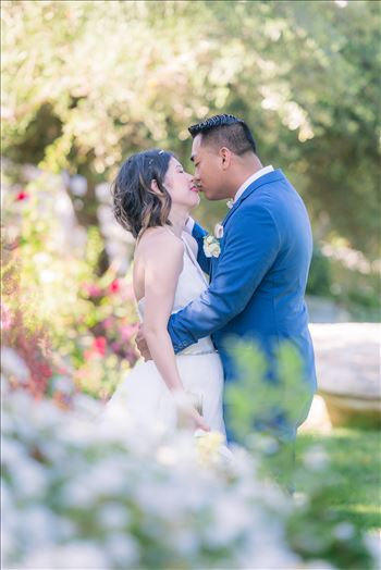 Mirror's Edge Photography captures Maryanne and Michael's magical wedding in the Secret Garden at the iconic Madonna Inn in San Luis Obispo, California.  Bride and Groom kiss in the garden