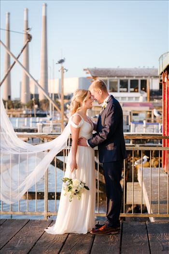 Sarah Williams of Mirror's Edge Photography, a San Luis Obispo Wedding and Engagement Photographer, captures Ryan and Joanna's wedding at the iconic Windows on the Water Restaurant in Morro Bay, California.  Bride and Groom with bay in background.