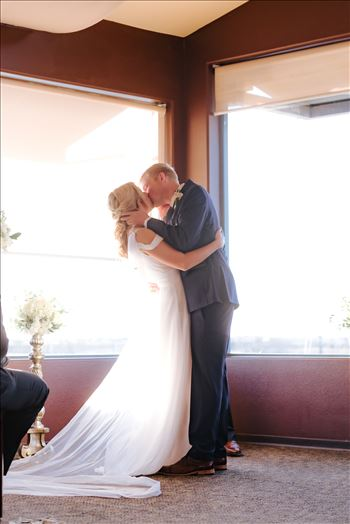 Sarah Williams of Mirror's Edge Photography, a San Luis Obispo Wedding and Engagement Photographer, captures Ryan and Joanna's wedding at the iconic Windows on the Water Restaurant in Morro Bay, California.  Bride and Groom kiss after I Do.