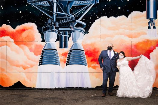 Sarah Williams of Mirror's Edge Photography and San Luis Obispo and Santa Barbara Wedding Photographer captures the Ochoa Wedding. Bride and Groom with Covid 19 Masks at Rocket Mural in Lompoc California.
