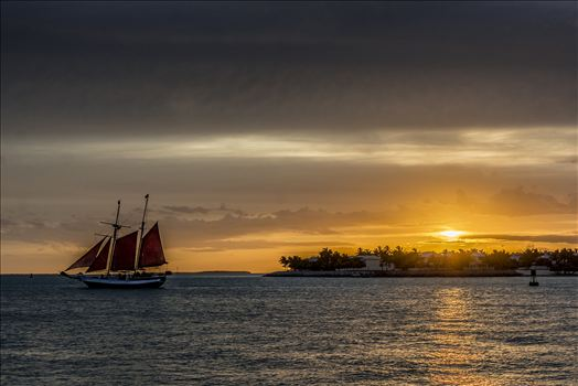 Key West sunset celebration with tall ships in the distance.