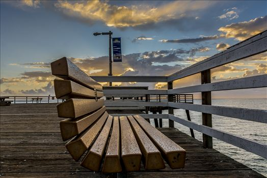 Rain slicked bench on Pismo Beach pier at sunset