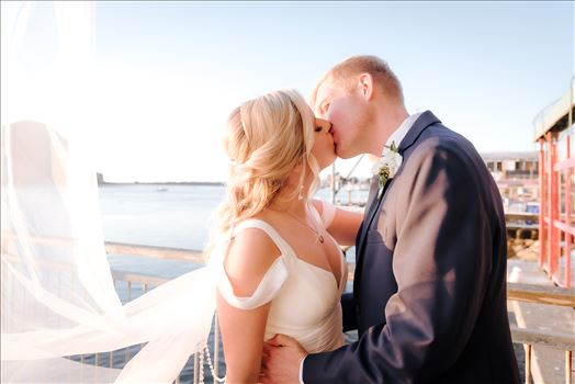Sarah Williams of Mirror's Edge Photography, a San Luis Obispo Wedding and Engagement Photographer, captures Ryan and Joanna's wedding at the iconic Windows on the Water Restaurant in Morro Bay, California.  Bride and Groom kiss with ocean in background